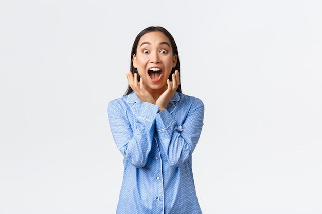 Aufgeregtes super glückliches asiatisches mädchen in blauen pyjamas, das zu einer großartigen überraschung aufwacht, vor glück schreit und erstaunt in die kamera schaut, auf ein tolles geschenk reagiert, weißer hintergrund steht.