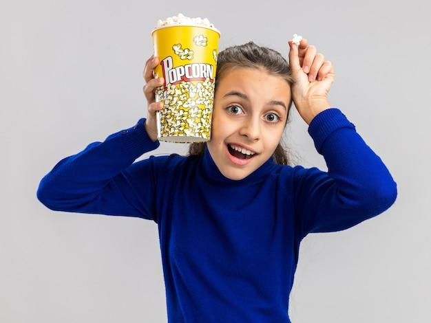 Aufgeregtes teenager-mädchen, das einen eimer mit popcorn und ein popcorn-stück hält, das den kopf mit dem popcorn-eimer und der hand isoliert auf weißer wand berührt