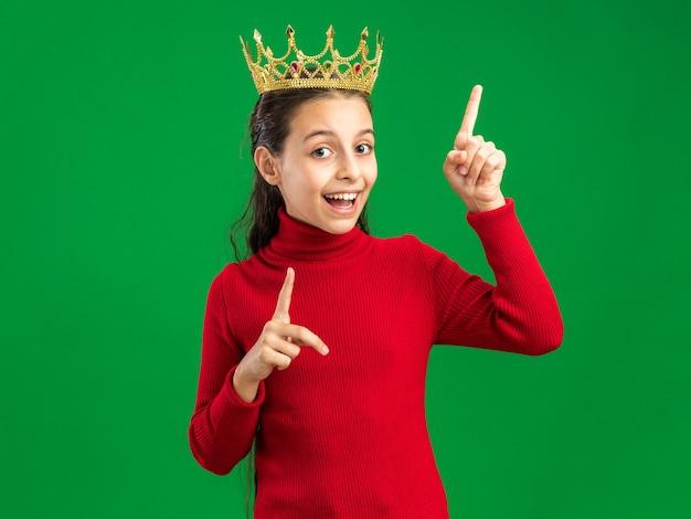 Aufgeregtes teenager-mädchen mit krone nach oben isoliert auf grüner wand mit kopierraum
