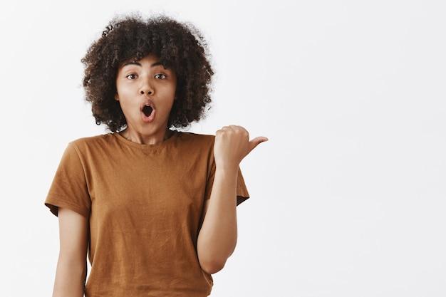 Aufgeregtes und fassungslos beeindrucktes dunkelhäutiges mädchen mit einer afro-frisur in braunem, trendigem t-shrit, das die geöffneten lippen mit dem daumen nach rechts zeigt und eine fantastische szene beschreibt, in der sie diese richtung sah