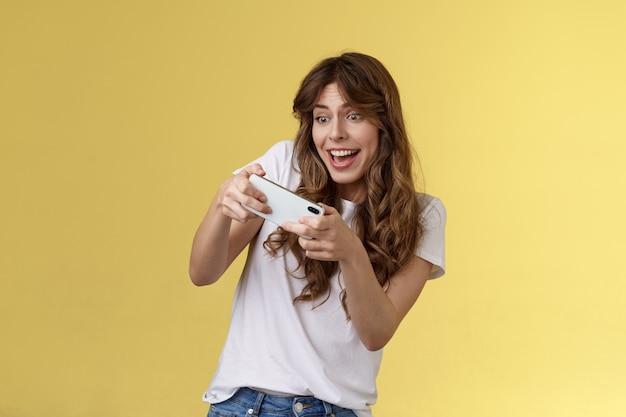 Aufgeregtes, verspieltes, enthusiastisches mädchen, das seitwärts kippt und tolles interessantes smartphone-spiel autorennen spielt, das lächelt, entschlossenes fokusspiel, handy horizontal tippen, gelber hintergrund halten