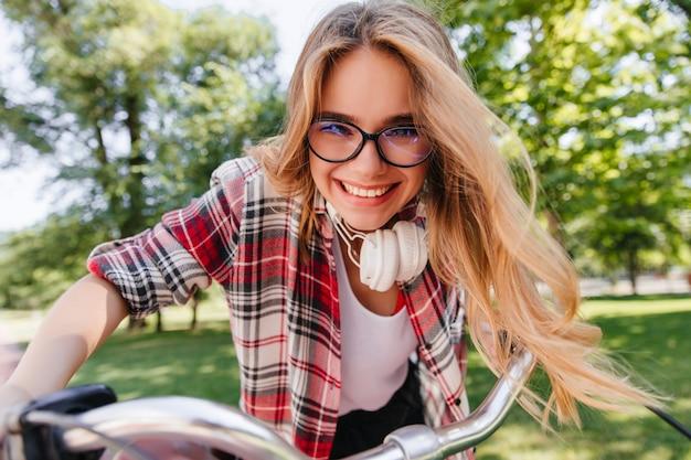 Aufgeregtes weibliches modell in brille und kopfhörern, die durch park reiten. emotionales blondes mädchen, das auf fahrrad sitzt und lacht.