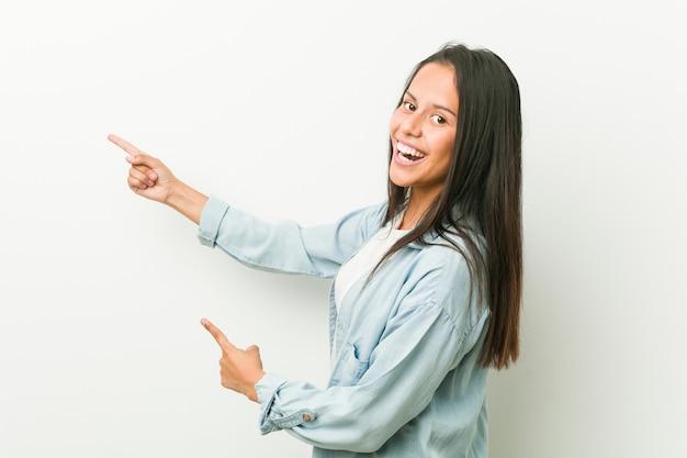 Aufgeregtes zeigen der jungen hispanischen frau mit den zeigefingern weg.