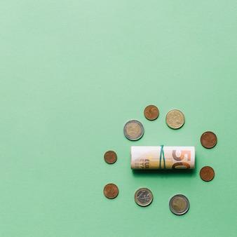 Aufgerollte euro-banknote mit münzen auf grünem hintergrund
