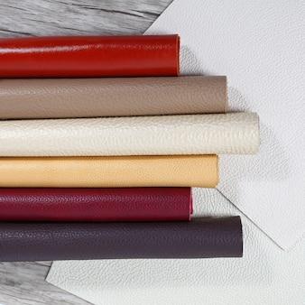 Aufgerollte naturleder-texturen in verschiedenen farben auf hellem holzhintergrund