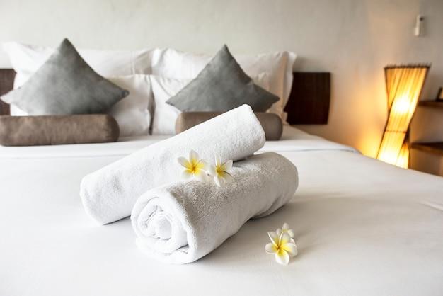 Aufgerollte saubere handtücher auf einem bett