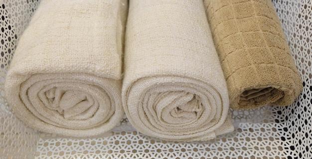 Aufgerollte weiße und braune frottier- oder baumwollbadetücher benutzt für das trocknen oder abwischen eines körpers.