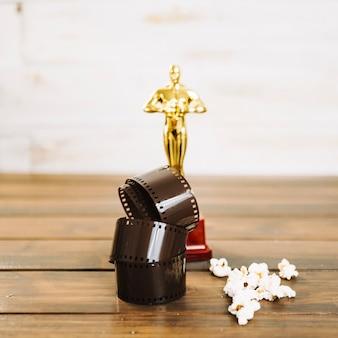 Aufgerollter film, popcorn und oscar-statuette