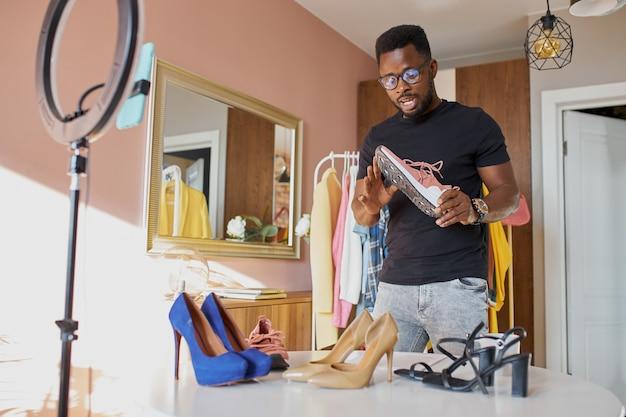Aufgeschlossener afro-blogger unterhält sich vor der kamera, zeigt neue klamotten und schuhe