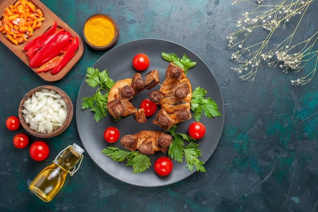 Aufgeschnittenes gekochtes fleisch der draufsicht mit grünen kirschtomaten und olivenöl auf dem blauen hintergrund