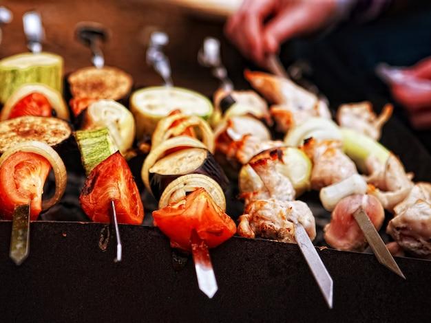Aufgespießtes fleisch und gemüse, die auf dem grill kochen