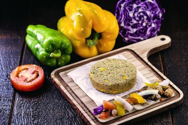 Aufgetauter veganer hamburger, frei ohne fleisch, hergestellt aus samen, gemüse, soja, kichererbsen, mais und litschi, umgeben von gemüse