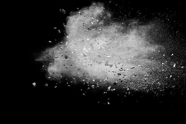 Aufgeteilter rückstand des steins explodierend mit weißem pulver gegen schwarzen hintergrund.