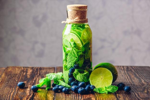 Aufgossenes wasser in der flasche mit limette, minze und blaubeere und allen zutaten auf dem tisch.