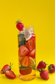 Aufgossenes wasser mit erdbeere und zitrone in der flasche