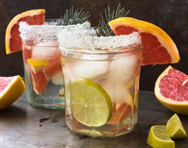 Aufgusswasser mit grapefruit und rosmarin in glasflasche auf grauem holztisch. diät gesunde ernährung und gewichtsverlust konzept, kopieren platz für text