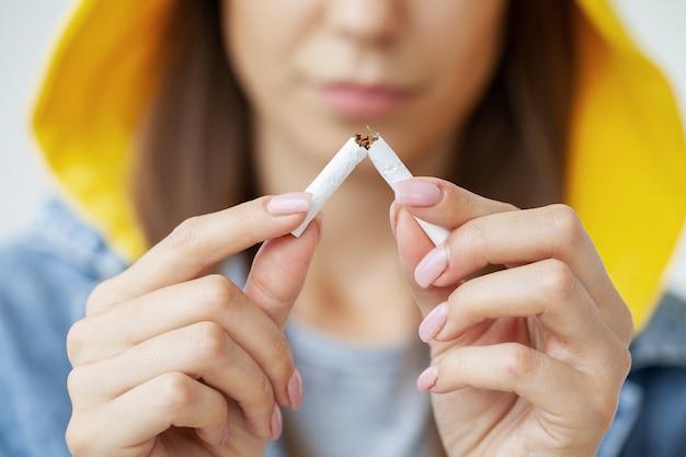 Aufhören zu rauchen, nahaufnahme von frau, die zigarette bricht