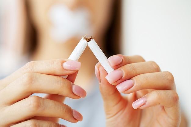 Aufhören zu rauchen, nahaufnahme von frau mit einer kaputten zigarette