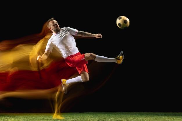 Aufholen. junger kaukasischer männlicher fußball- oder fußballspieler in sportbekleidung