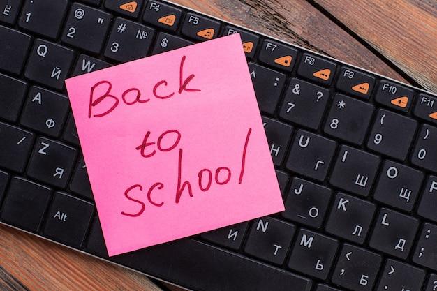 Aufkleber mit handschrift zurück zur schule auf einer pc-tastatur. alter schreibtisch aus holz.