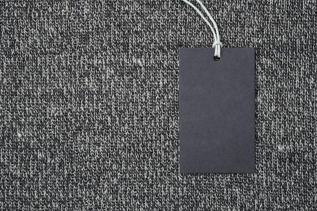 Aufkleber oder tag des leeren papiers auf gestrickter wolle kleidet hintergrund