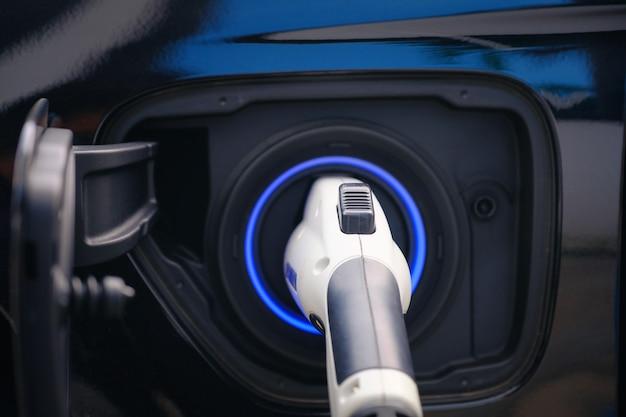 Aufladen der modernen elektroautobatterie auf der straße, die die zukunft des automobils sind, abschluss oben der stromversorgung verstopft in ein elektroauto, das für hybrid aufgeladen wird. neue ära des fahrzeugtreibstoffs.