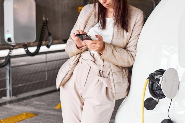 Aufladen des elektroautos auf dem parkplatz. junge frau, die auf das aufladen des umweltfreundlichen automobils und das verwenden ihres smartphones wartet.