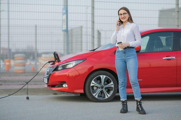 Aufladen des elektroautos in der straße. ökologisches auto angeschlossen und batterien aufgeladen. mädchen verwenden kaffeegetränk, während sie smartphone verwenden und auf die stromversorgung warten. zum aufladen mit elektrofahrzeugen verbinden
