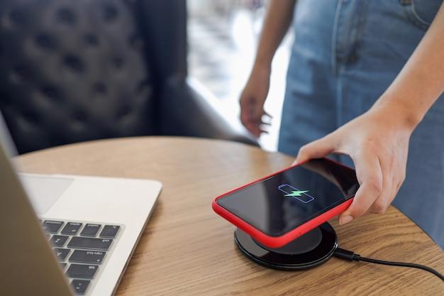 Aufladen des handyakkus mit drahtlosem gerät in der tabelle. aufladen des smartphones auf einem ladepad. mobiltelefon in der nähe des kabellosen ladegeräts.