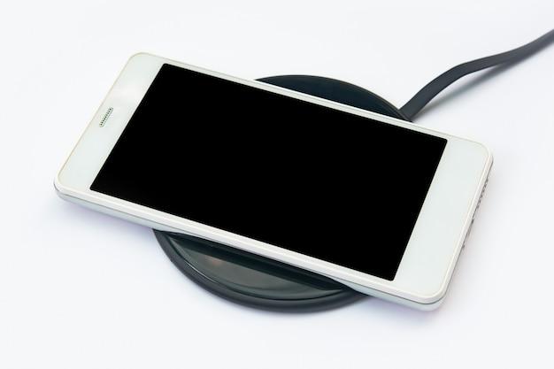 Aufladen des smartphones auf einem kabellosen ladegerät auf weiß