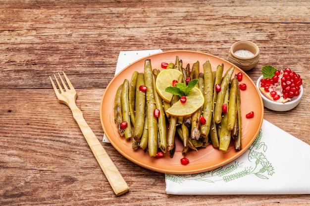 Auflauf mit grünen bohnen, sesam, granatapfel, minze und zitrone