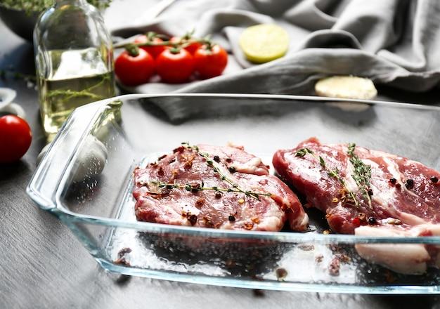 Auflaufform mit frischen rohen steaks auf dem tisch