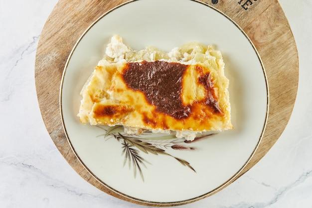 Auflaufkuchen mit käse und sauerampfer auf teller auf hellem hintergrund.