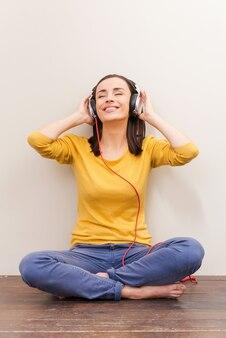 Auflösen in schöner musik. schöne junge frau mit kopfhörern, die die augen geschlossen hält, während sie auf dem boden vor braunem hintergrund sitzt