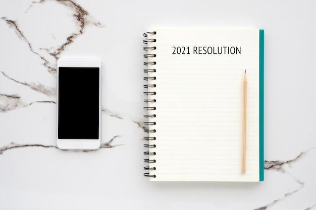 Auflösung 20121 auf leerem notizbuchpapier, smartphone mit leerem bildschirm auf weißem marmor