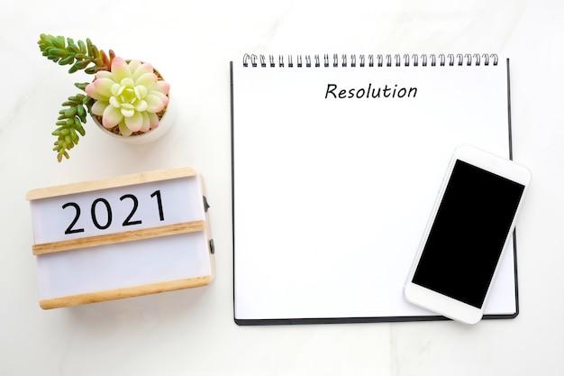 Auflösung 2021 auf leerem notizbuchpapier, smartphone mit leerem bildschirm auf weißem marmor