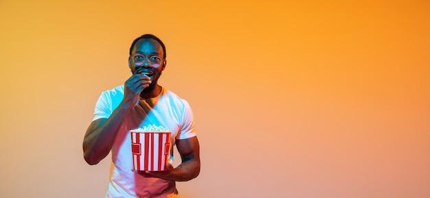 Aufmerksam, aufgeregt. modernes porträt des afroamerikanischen mannes auf orangefarbenem studiohintergrund mit farbverlauf im neonlicht. schönes afro-modell. konzept von emotionen, kino, gesichtsausdruck, verkauf, anzeige. flyer.
