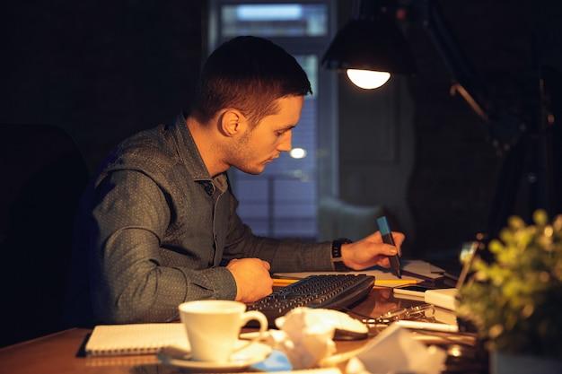 Aufmerksam. mann, der während der coronavirus- oder covid-19-quarantäne allein im büro arbeitet und bis spät in die nacht bleibt. junger geschäftsmann, manager, der aufgaben mit smartphone, laptop, tablet im leeren arbeitsbereich erledigt.