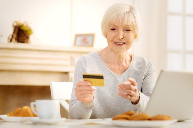 Aufmerksam sein. positiv entzückte ältere frau, die kreditkarte hält, während sie das gleichgewicht überprüft und gefühle ausdrückt
