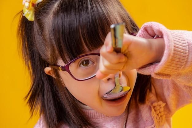 Aufmerksam suchen. entzückendes junges mädchen mit braunen augen, die mit down-syndrom leiden und morgenbrei essen