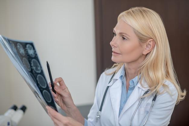 Aufmerksame denkende frau mit langen blonden haaren im medizinischen kleid, das mrt-scan in der hand in der arztpraxis hält