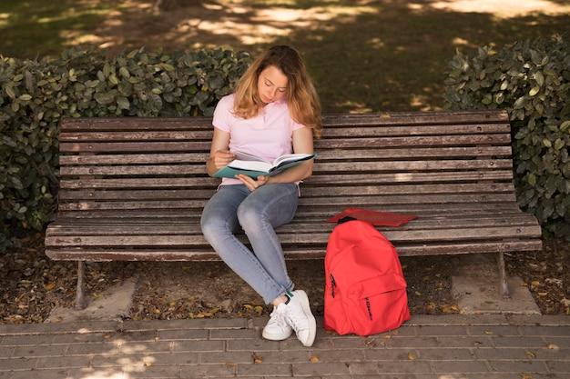 Aufmerksame jugendlich frau mit lehrbuch auf bank