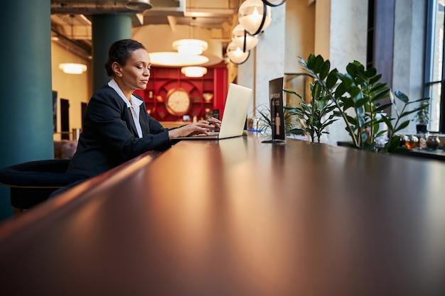 Aufmerksame junge assistentin, die auf die tastatur starrt, während sie eine nachricht für ihre partner schreibt