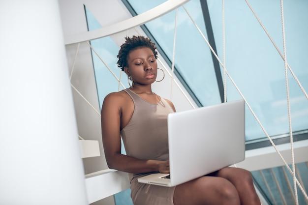 Aufmerksame junge erwachsene frau mit laptop im büro
