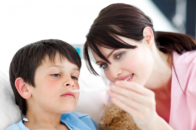 Aufmerksame krankenschwester und sein patient, die einen thermometer betrachten
