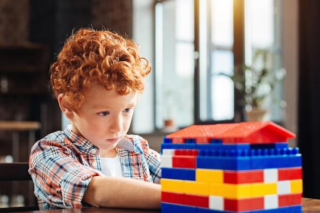 Aufmerksame prüfung. selektiver fokus auf ein völlig in den untersuchungsprozess vertieftes kind, das seine aufmerksamkeit auf ein buntes plastikhaus richtet