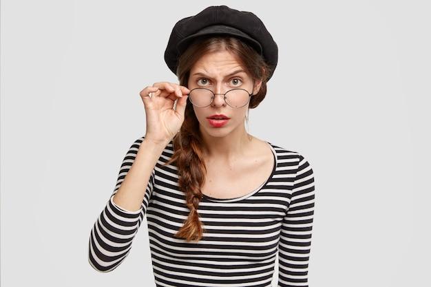 Aufmerksame strenge lehrerin für französisch schaut gewissenhaft durch brillen, trägt gestreiften pullover und baskenmütze