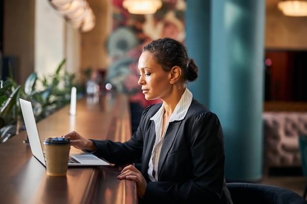 Aufmerksame weibliche person, die in halber position vor ihrem computer sitzt und die antwort auf die nachricht eintippt