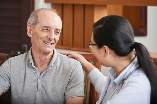 Aufmerksamer doktor, der älteren patienten beruhigt