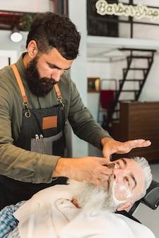 Aufmerksamer friseur, der dem kunden im friseursalon bart rasiert